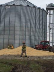 Workers cut a hole in the side of a grain bin in order