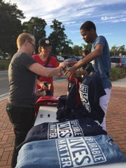 Trump supporters buy shirts during Wednesday's Trump rally at the amphitheater at Maritime Park.
