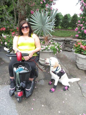 Alexandra Joyce with her service dog, Shandy. Joyce was diagnosed at age 9 with Charcot-Marie-Tooth, an inherited disease that damages nerves.