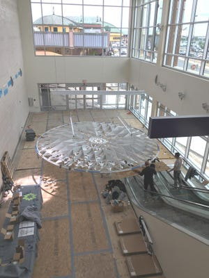 """Workers install the """"Radiance"""" public art work at the El Paso International Airport."""
