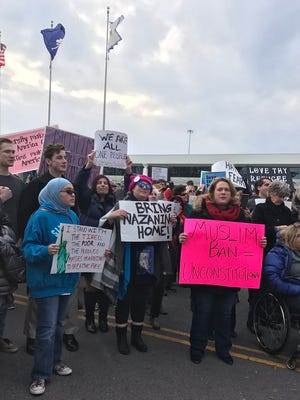 About 200 people gathered at the airport for a protest to support immigrants and refugees.