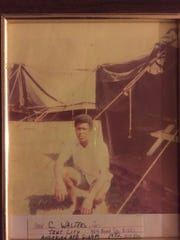 """Cleveland Walters poses by his tent in """"Tin City"""" on Andersen Air Force Base. Walters alleges that he personally sprayed Agent Orange in Tin City and around the base."""