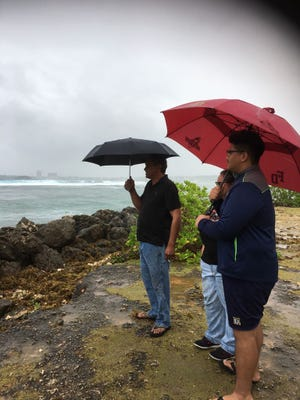 Ricardo Ignacio, Linda Perez and Daraven Perez watch the waves in Hagåtña Saturday morning.