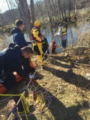 Emergency responders equipped with water rescue gear deployed a rope system across the creek due to the rapidly moving water.