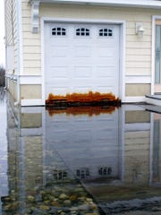 This April 26, 2017 photo shows a garage door on a home in Ocean City on the edge of a back bay that floods regularly, and has rusted the metal door. Scientists and people living in back-bay areas behind barrier islands say flooding is increasing, even as the problem gets less attention and money than flooding along the ocean.