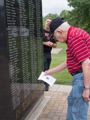 A man checks names on the Delhi Veterans Memorial during