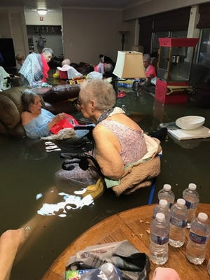 Residents of La Vita Bella assisted living facility in Dickinson, Texas, sit in waist-deep water Aug. 27, 2017, waiting for help.