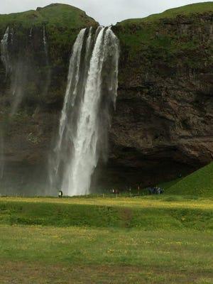 A waterfall cascades over rock in Reykjavík, Iceland.