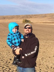 Kyle Wasson holds his son Barrett on farmland near Loring. Wasson was among the rural customers dropped by Verizon.