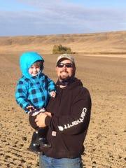 Kyle Wasson holds his son Barrett on farmland near
