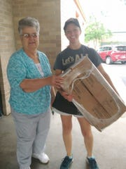 Barb Thill, left, stands with A&W team member Becky Reddig with one of several cases of the bags A&W donated to hold Brown Bag Lunches. This year, A&W donated over 15,000 bags.