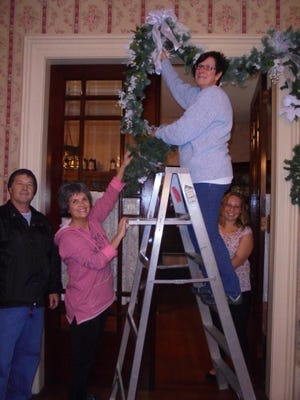 Tim Musselmanwatches as Susan Maynard, June Gebhardt (on ladder) and Sara Gebhardtmanage a huge garland going up in the parlor archway at the Bucyrus Historical Society. The public is invited to visit during the holiday open house, 1 to 4 p.m. Dec. 3.