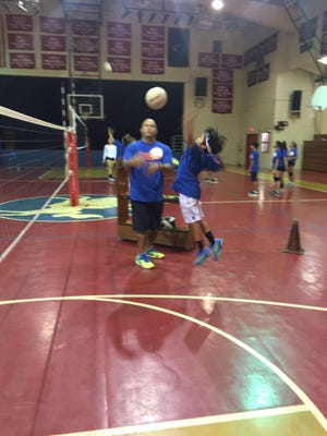 In this file photo, coach Mike Rabago works on a quick-set drill with Masato Rabago during a recent youth clinic. The Guam Volleyball Federation is sponsoring a free jamboree Sunday at the UOG Calvo Field House