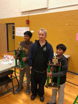 Chess Coach and International Master Ron Burnett, center, stands with Tennessee chess champions for their age groups, Arya Jalem, left, and Aditya Jalem.