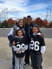 Saquon Barkley poses with family friend Alicia Knauff and her daughters Jade, left, and Amaya before a Penn State football game.