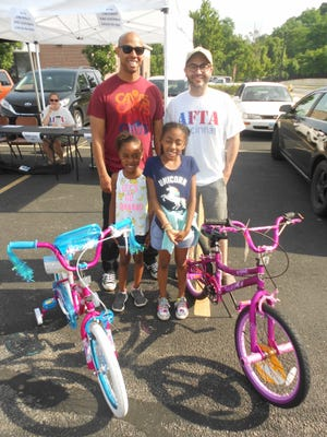 (At left) Gary Johnson's daughters Zaria Johnson, 7, and Zoelle Johnson, 10, were bike recipients last year. They are with AFTA volunteer Daniel Tonozzi (at right).