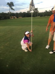 Pensacola resident Janelle Flores celebrates with her playing partners after she picks up the golf ball from the No. 8 hole at Scenic Hills Country Club after she made a hole-in-one July 16 , along with Scott Ames in a Monday Night Golf League.