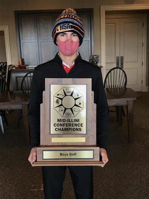 Pekin's Mason Minkel holds the Mid-Ilini Conference boys golf championship traveling trophy after the Dragons won the conference tournament Thursday at Metamora Fields Golf Club.