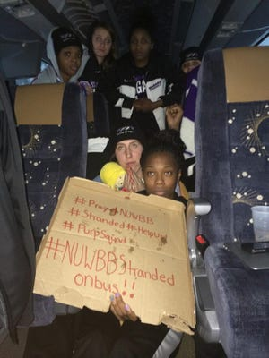 This photo provided by Chelsea Andorka, the Niagara University women's basketball team spokeswoman, shows the team holding a sign while their bus was snowbound on the New York State Thruway in the middle of a lake-effect storm that has dropped more than 4 feet of snow near Lackawanna, N.Y., Tuesday. Pictured at the bottom right, holding the cardboard sign, is Sylvia Maxwell. Taylor McKay is pictured top left. Both are 2012 Waverly High School graduates.