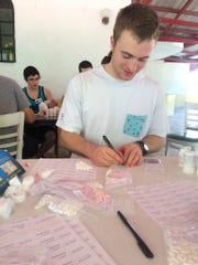 Jared Wagoner, a Corban University student, counts medication for the week's mobile clinics. A class from Corban operated daily clinics in Haiti during spring break.