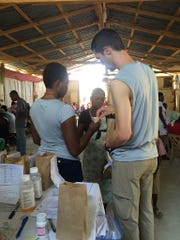 Timothy Fouch, registered nurse, explains medications to a patient at the pharmacy station using an interpreter. Fouch accompanied Corban University students on a mission trip to Haiti over spring break.