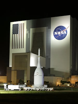 The Orion spacecraft moves by the Vehicle Assembly Building on its journey from the Launch Abort System Facility at the Kennedy Space Center to Space Launch Complex 37B at the Cape Canaveral Air Force Station on Nov. 11, 2014, in Cape Canaveral, Fla.