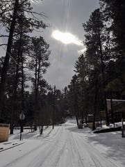 The sun peeks through the clouds after Ruidoso receives about an inch of snow Friday morning.