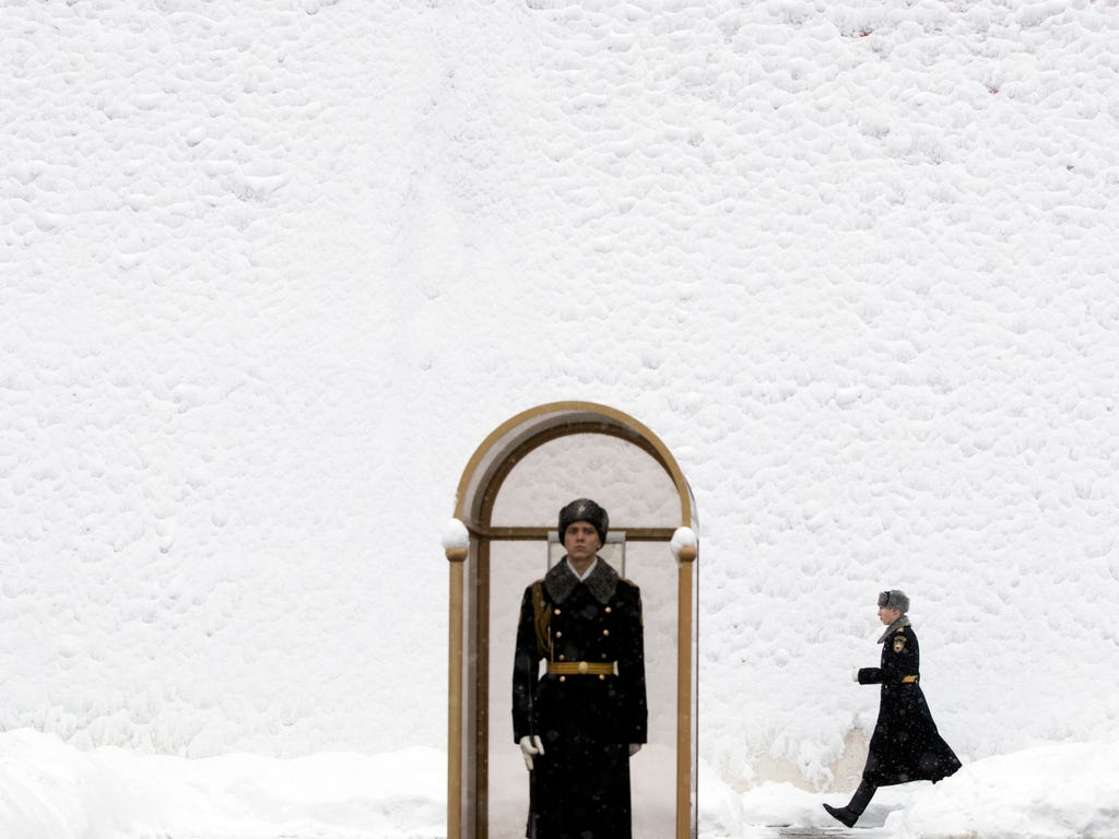 An Honor guard soldier walks along the Kremlin wall as his fellow soldier stands at the Tomb of Unknown Soldier in Moscow, Russia. According to forecasts snowfalls and blizzard will continue in Moscow through the next several days with temperatures d