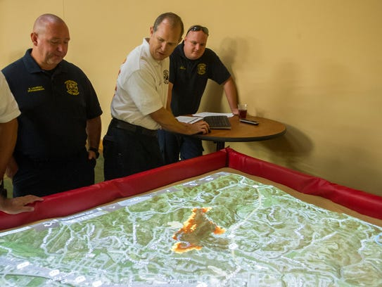 Lt. Kevin Nunn, center, of the Pigeon Forge Fire Department demonstrates the wildfire simulation model used by Gatlinburg officials to guess the path of the oncoming wildfire. The results showed the fire reaching the city in 19 hours; flames breached the city limits within 90 minutes.
