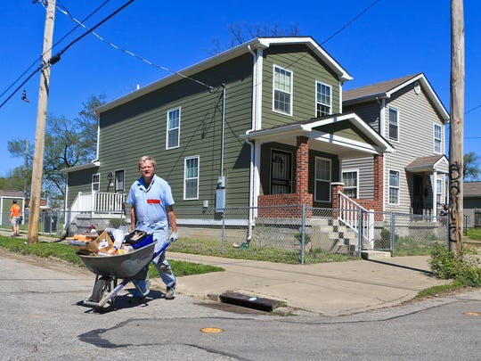 Volunteer Dave Ruhl pushes a wheelbarrow at the intersection of Caldwell and Hancock Streets while working in the Smoketown neighborhood Saturday as part of Give A Day.
