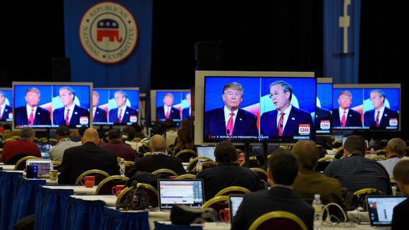 Donald Trump and Jeb Bush are seen on television monitors