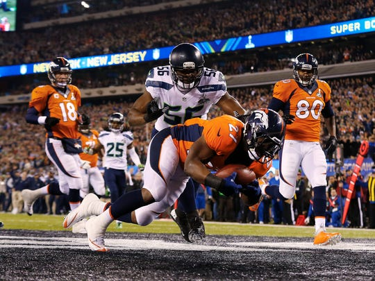 Denver Broncos running back Knowshon Moreno (27) jumps on a fumbles snap as Seattle Seahawks defensive end Cliff Avril (56) prepares to make the tackle for a safety on the first play of Super Bowl XLVIII, Feb. 2, 2014.