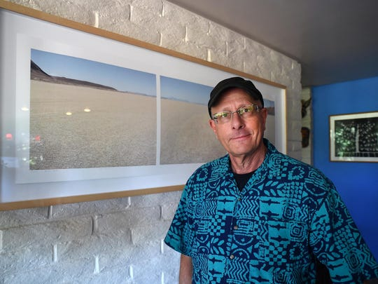 Peter Goin, a professor of Art at UNR, stands next to his photograph of the Black Rock Desert at his Reno home. Goin had been photographing Burning Man for years and had produced documentaries on the yearly event.