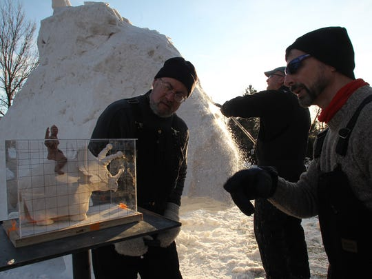 Team USA Snow Sculptors, from left, Michael Sponholtz, Milwaukee, Tom Queoff, Milwaukee, and Mike Martino, La Crosse, work on turning the model of a boy riding a ticeratops, left, into a snow sculpture in 2012 at the Woodson Art Museum in Wausau.