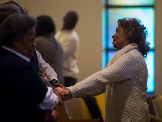Dr. Shirley Napier joins hands with those in the pew