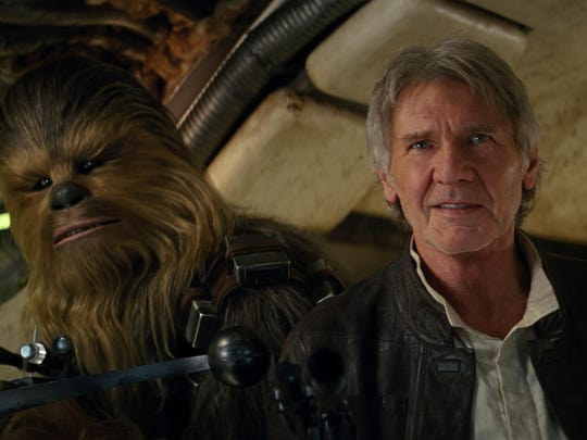 "Chewbacca (Peter Mayhew, left) and Han Solo (Harrison Ford) return to the Millennium Falcon in ""Star Wars: The Force Awakens."""