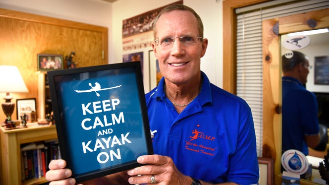 Rick Rassier holds a sign he keeps in his St. Cloud office. Rassier is a motivational speaker and a freestyle kayaker.