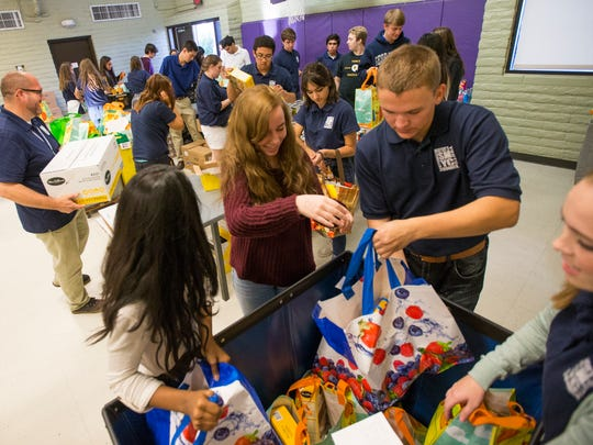 Members of the Scottsdale Mayor's Youth Council help package ingredients for over 300 Thanksgiving meals at Vista del Camino in Scottsdale on Nov. 17, 2014.