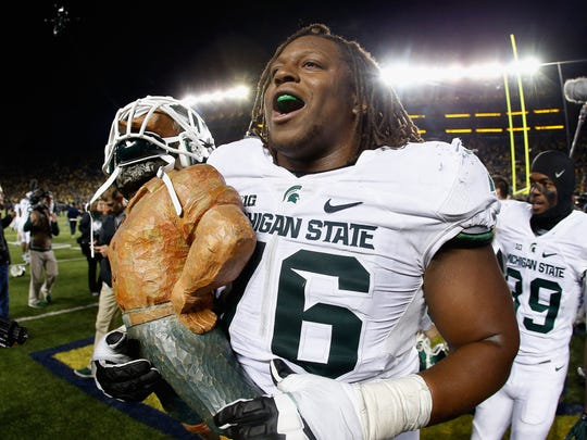Offensive lineman Donavon Clark of Michigan State celebrates with the Paul Bunyan Trophy after defeating the Michigan Wolverines, 27-23.