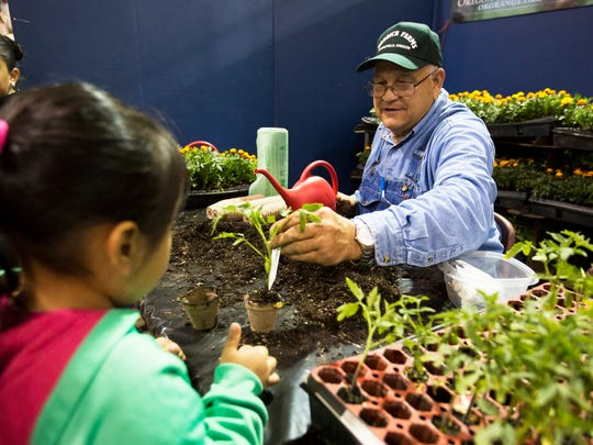 Vernon Herrick helps visitors plant small tomato plants at a booth for the Oregon State Grange at the Ag Fest on Saturday, April  23, 2016 at the State Fairgrounds. The annual two day event is full of demonstrations, activities and educational opportunities all centered around agriculture.
