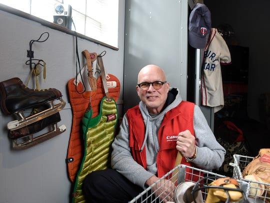 Dan Stephenson smiles next to vintage sports props