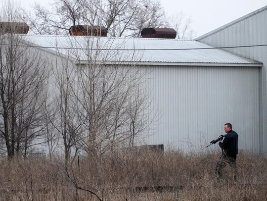 A police officer walks in the tall grass near Hazen
