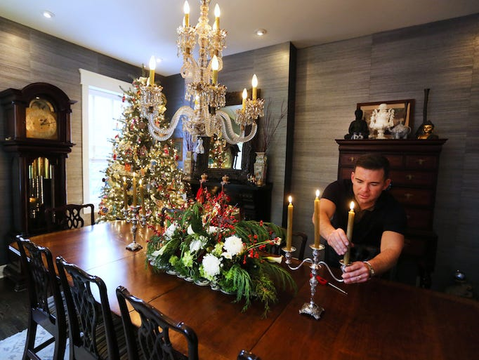 Ryan Messer lights candles in the formal dining room