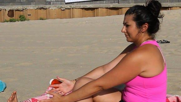 Reporter Kala Kachmar doing yoga on the beach in Avon.