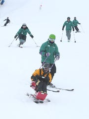 Wounded Iraqi war veteran Timothy Birckhead enjoys his ride down the mountain as Adaptive Sports Foundation volunteer instructor Eric Heym holds on to him at Windham Mountain.