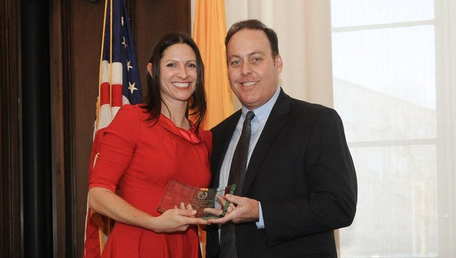 Sean Sullivan, the Catholic University Associate Vice President and Director of Athletics, gives Cristine Kosnik an award as she is inducted into the school's hall of fame.