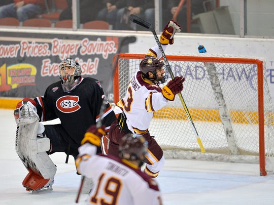 Minnesota-Duluth's Tony Cameranesi (13) celebrates a goal by teammate Brenden Kotyk on St. Cloud State goalie Charlie Lindgren (35) in the first period Friday night at the Herb Brooks National Hockey Center in St. Cloud.