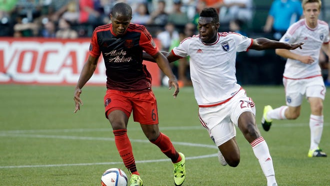 Portland Timbers forward Darlington Nagbe, left, and San Jose Earthquakes midfielder Fatai Atashe chase down the ball during the first half of an MLS soccer game in Portland, Ore., Sunday, July 5, 2015. (AP Photo/Don Ryan)