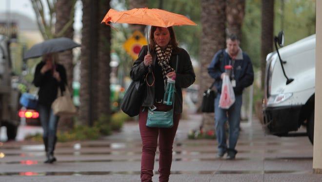 A woman walks to work in the rain in Phoenix, Arizona on December 14, 2015.