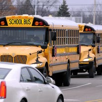 School buses head  toward Holt High School. The resurfacing of Holt Road this year between the business district and the high school will include have the entire stretch being converted to three lanes that include a left-turn lane. Construction is scheduled from August to October.
